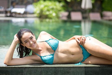 쾌활한 젊은 여성이 수영장에서 포즈 스톡 콘텐츠
