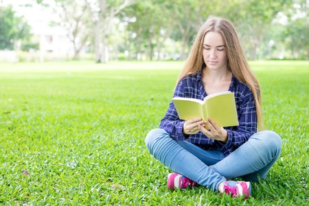 Concentrated student girl reading interesting book 版權商用圖片