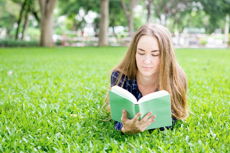 Concentrated young woman resting with book in park