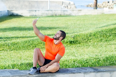 Content strong man making selfie outdoors