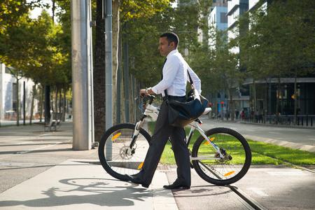 Hispanic Office Worker with Bike Crossing Street 版權商用圖片