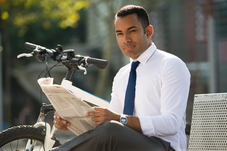 Smiling Latin Businessman with Newspaper in Park