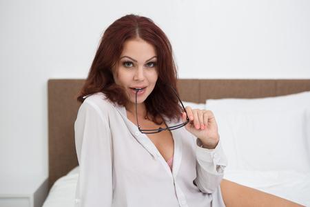 Sensuelle jeune femme portant chemise mordre des lunettes Banque d'images - 86747760