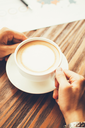 Male hands with coffee cup at desk Stock Photo