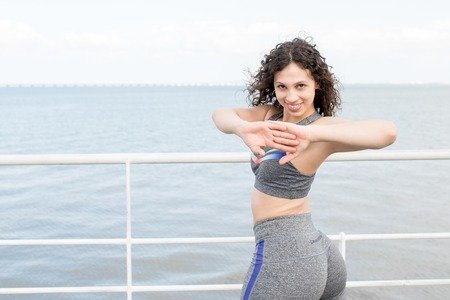 Positive Sporty Woman Exercising on Quay Stock Photo