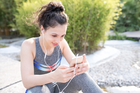 Content Sporty Girl Listening to Music in Park Stock Photo