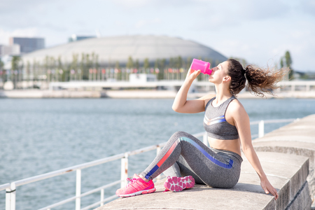 Pretty Sporty Woman Drinking by City River Stock Photo