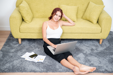 Cheerful young female freelancer working at home