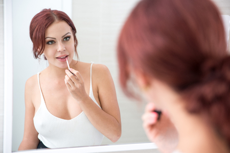 Concentrated woman applying lipstick at mirror