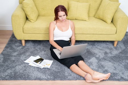 work life balance: Confident businesswoman working on floor at home