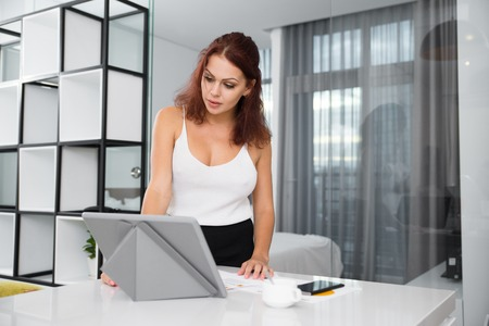 work life balance: Sexy Woman Standing at Table With Tablet at Home