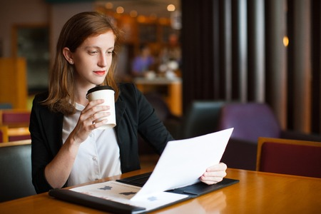 work life balance: Confident businesswoman reading paper at cafe
