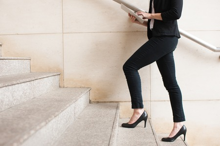 Businesswoman walking upstairs and using touchpad