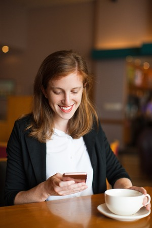 work life balance: Happy businesswoman reading phone message at cafe