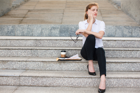 work life balance: Displeased young businesswoman sitting on stairs