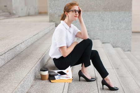 work life balance: Pensive young businesswoman sitting on staircase