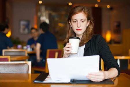 work life balance: Serious businesswoman reading document at cafe