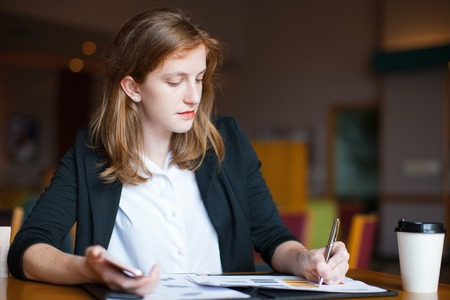work life balance: Serious young businesswoman making notes at cafe