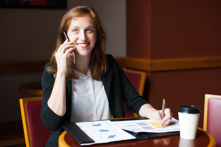 work life balance: Smiling businesswoman talking on phone in cafe Stock Photo