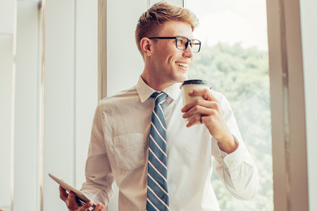 Happy Business Man With Cup and Tablet at Window Stock Photo