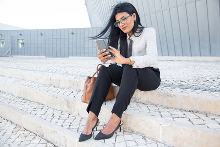 Pleased businesswoman responding to sms on phone Stock Photo