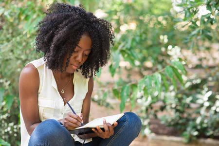 african business: Serious Young Black Woman Working in Park Stock Photo
