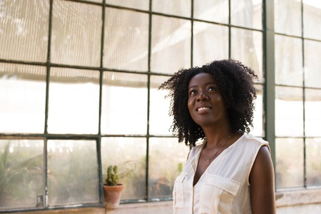 african business: Portrait of happy young woman looking away indoors Stock Photo