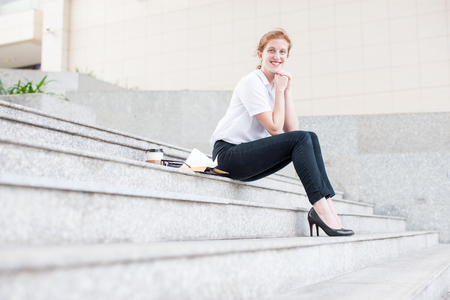 Smiling Business Woman Sitting on Stairs Outdoors Stock Photo