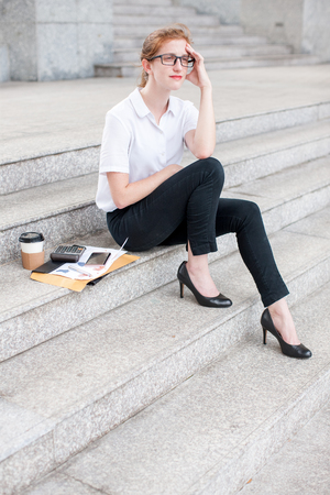 tired: Pensive Business Woman Sitting on Stairs Outdoors