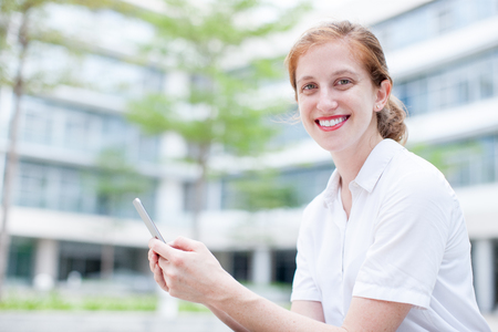 Smiling Female Student Using Smartphone in City Stock Photo