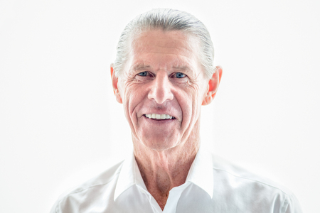 Cheerful senior businessman smiling at camera Stock Photo