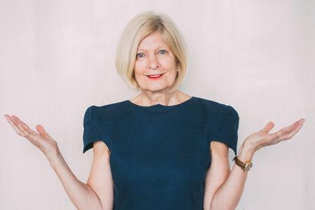Smiling senior businesswoman shrugging shoulders Stock Photo