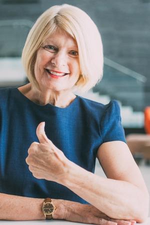 Cheerful senior businesswoman showing thumb-up