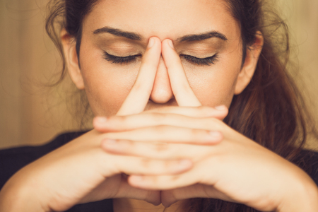 Close-up of tired young woman rubbing nose Stock Photo