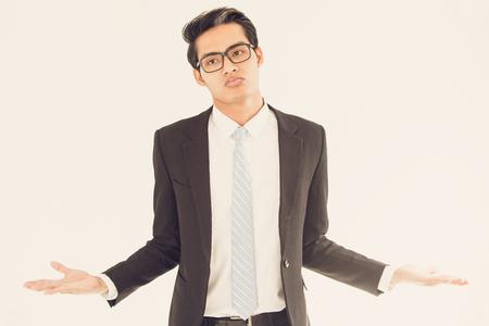 Misunderstanding Asian businessman shrugging arms