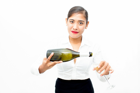 Confident young waitress pouring champagne in flute