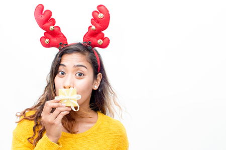 Grimacing woman covering mouth behind gift box