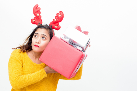 Curious pretty woman shaking Christmas gifts