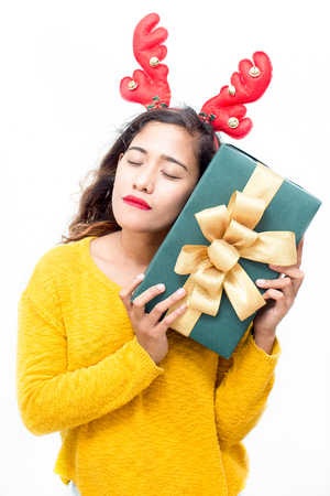 Dreamy attractive woman embracing Christmas gift