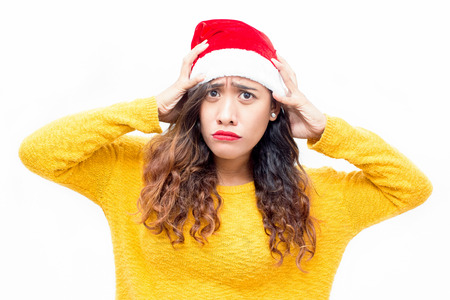 Offended young woman in Santa hat pouting