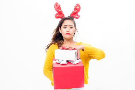 Uncertain young woman carrying Christmas presents Stock Photo