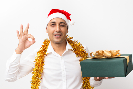 Happy Man Showing OK Sign With Gift Box and Tinsel