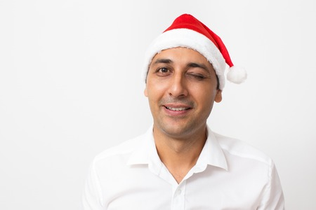 Smiling handsome manager in Santa hat winking