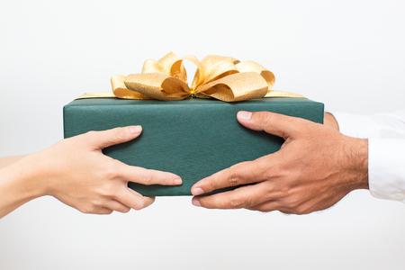 Paar dat verpakt kerstcadeau bij elkaar houdt Stockfoto