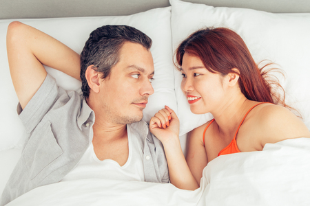 Smiling Couple Chatting and Lying in Bed Stock Photo