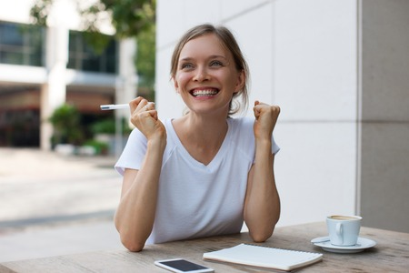 Cheerful Woman Finding Solution in Outdoor Cafe