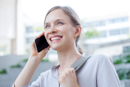 Happy ambitious lady having phone conversation Stock Photo