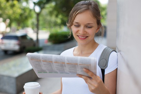 Positive Woman Reading Newspaper Outdoors Stock Photo