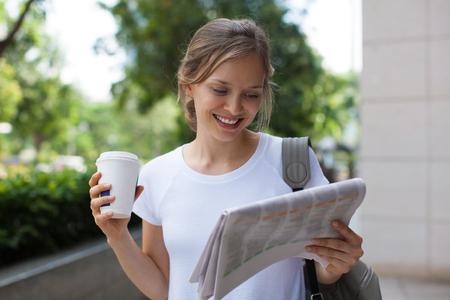 Positieve vrouw lezing krant op straat Stockfoto