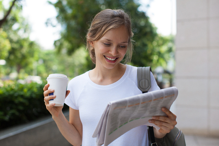 Positive Woman Reading Newspaper on Street Standard-Bild
